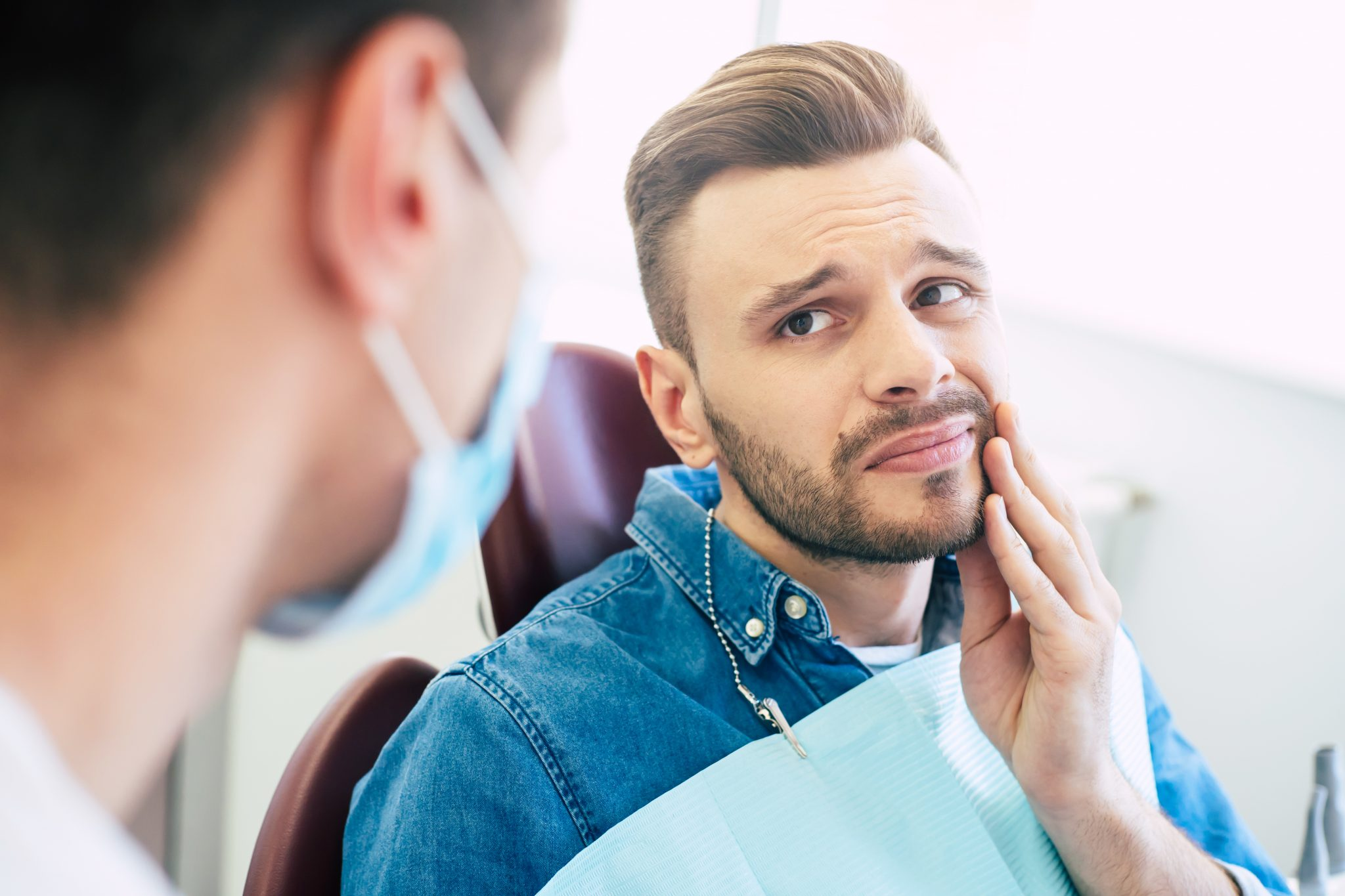 Symptoms Of Gums Pain. A Man With A Worried Face Is Holding His Hand On His Cheek Because Of Irritating Pain In Front Of A Dentist Who Is Going To Give A Patient A Treatment.